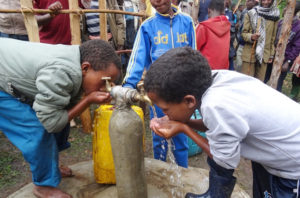 Kinder die vom Brunnen Wasser trinken