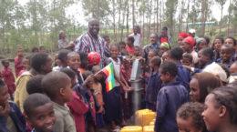 Missionar und viele Kinder am Brunnen