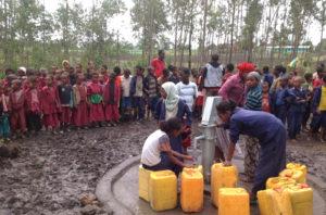 Viele Kinder und Frauen mit Kanistern an einem Brunnen